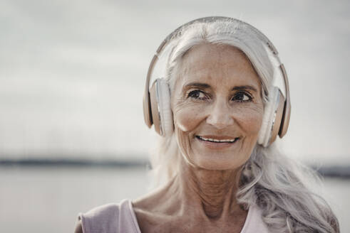 Senior woman listening music with headphones at the sea, poartrait - JOSF03662