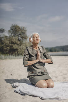 Senior woman meditating with headphones on the beach - JOSF03689