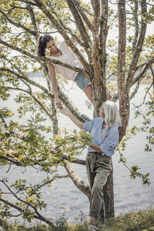 Mother watching daughter, climbing in a tree - JOSF03707
