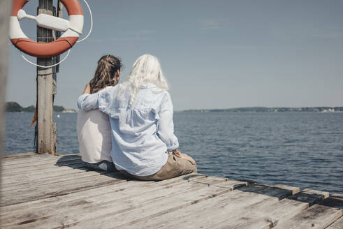 Mother and daughter looking at the sea, sitting on jetty, rear view - JOSF03710