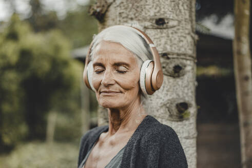 Senior woman relaxing in nature, listening music with headphones - JOSF03719
