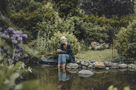 Woman relaxing at garden pond, drinking tea - JOSF03722