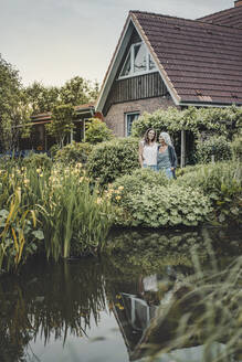 Mother and daughter standing in garden, inf ront of their house - JOSF03725