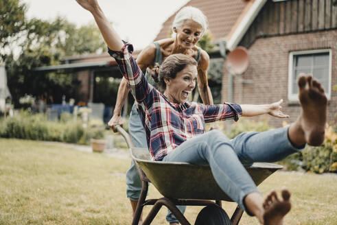 Mother pushing daughter, sitting in push cart, through he garden - JOSF03728