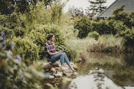 Woman sitting at garden pond, using digital tablet - JOSF03731