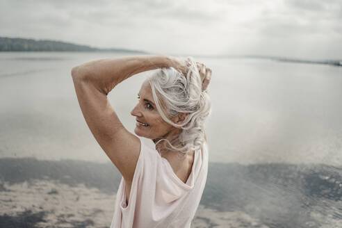 White haired senior woman posing by the sea - JOSF03746