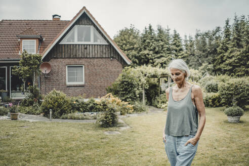 Senior woman walking her garden, with hands in pockets - JOSF03779