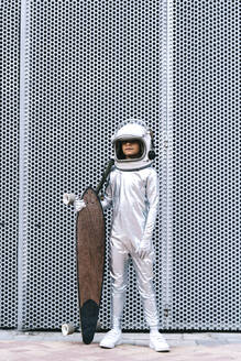 Kid dressed as an astronaut with longboard - DAMF00036