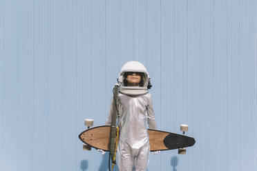 Kid dressed as an astronaut with longboard - DAMF00039