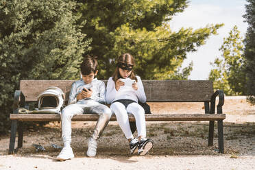 Two kids in astronaut and superhero costumes using mobile phone on park bench - DAMF00048