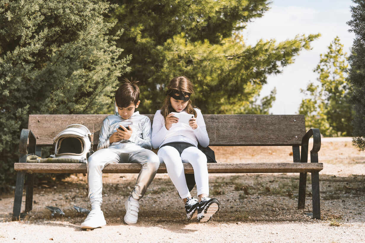 Two kids in astronaut and superhero costumes using mobile phone on park bench - DAMF00048 - David Agüero Muñoz/Westend61
