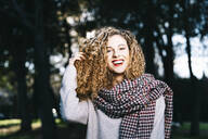 Portrait of laughing young woman with ringlets in a park - DAMF00051