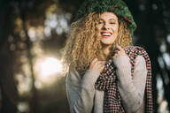 Portrait of laughing young woman wearing Christmas wreath on her head - DAMF00054