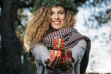 Portrait of smiling young woman with Christmas wreath on her head presenting Christmas present - DAMF00057