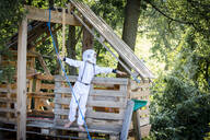 young, cool boy dressed as a superhero astronaut playing in a beautiful, tree house in the afternoon sun, lower austria, austria - HMEF00542