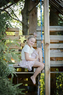 pretty girl dressed as a princess with crown and sceptre playing in a beautiful, tree house in the afternoon sun, lower austria, austria - HMEF00560