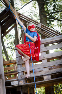 beautiful superhero girl playing in a beautiful, tree house in the afternoon sun, lower austria, austria - HMEF00563
