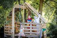 three cool kids with superheroes costumes playing on their homemade tree house, in the afternoon sun, lower austria, austria - HMEF00569