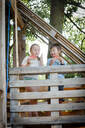 Girl and boy eating watermelon in tree house - HMEF00572