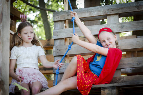 Girls dressed up as princess and superwoman playing in a tree house - HMEF00575