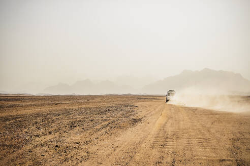Off-road vehicle moving on arid landscape against clear sky, Suez, Egypt - PUF01716