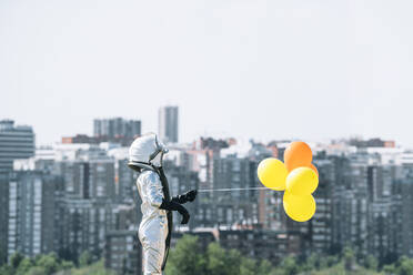 Boy dressed as an astronaut holding balloons in the city - JCMF00208