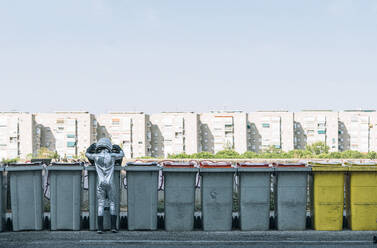 Rear view of boy dressed as an astronaut at garbage cans in the city - JCMF00211