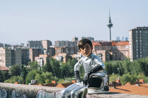Portrait of boy dressed as an astronaut sitting on a wall in the city - JCMF00214