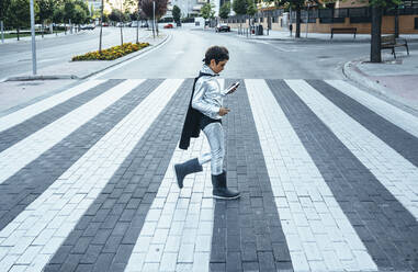 Portrait of boy disguised as superhero crossing a street the city - JCMF00217