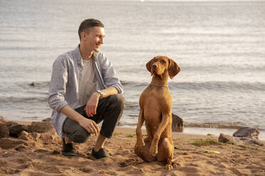 Young man with his dog at the beach during training - VPIF01525
