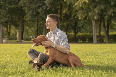 young man with his dog, cuddling on a meadow - VPIF01531