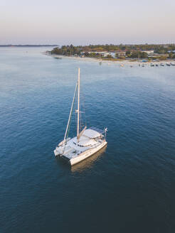 Aerial shot of catamaran on sea at Gili-Air Island against clear sky during sunset, Bali, Indonesia - KNTF03442