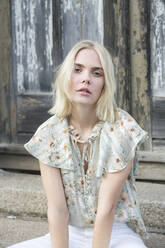 Portrait of blond young woman wearing summer blouse with floral design - JESF00317