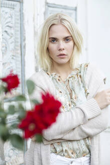 Portrait of blond young woman wearing summer blouse with floral design and cardigan - JESF00320