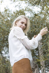 Portrait of blond young woman wearing white blouse outdoors - JESF00326