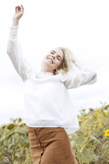 Portrait of blond young woman wearing white blouse dancing on sunflower field - JESF00329
