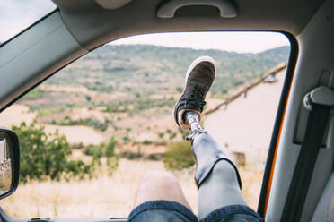 Legs of prosthetic young man dangling out of camper van window - CJMF00014