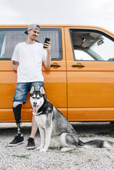 Young man with dog wearing leg prosthesis and using cell phone at camper van - CJMF00017