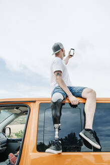 Young man with leg prosthesis sitting on roof of camper van using cell phone - CJMF00023