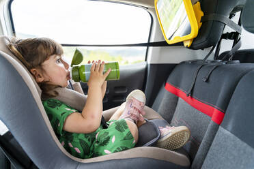 Toddler girl sitting on a car seat with a mirror drinking water - GEMF03149