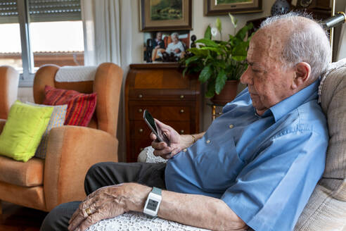 Elderly man using a mobile phone and wearing a smart emergency alarm bracelet around wrist at home - GEMF03152