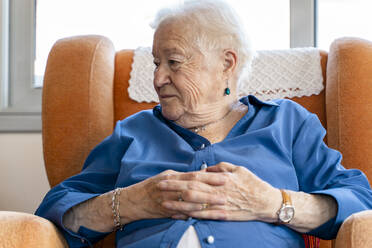 Elderly woman sitting in an armchair in living room - GEMF03158