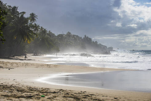 Scenic view of waves splashing at shore against cloudy sky at Trinidad and Tobago, Caribbean - RUNF03190