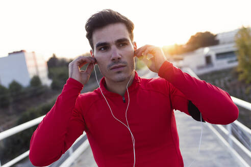 Portrait of sporty young man listening to music in the street. LLeida, catalonia, Spain - JSRF00595