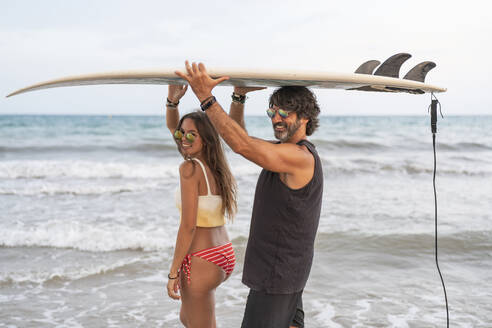 Young woman and mature man carrying surfboard together at the sea - DLTSF00145