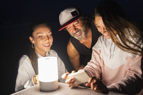 Two young women and mature man with smartphone and led light on camping table at night - DLTSF00160