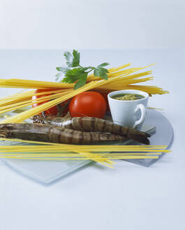 Close-up of ingredients for cooking spaghetti with shrimp and pesto on table - PPXF00284