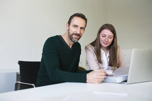 Portrait of confident businessman and employee working at desk in office - MIKF00002