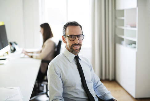 Portrait of confident businessman in office with employee in background - MIK00005