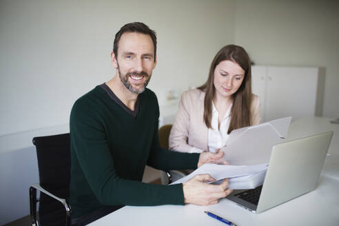 Portrait of smiling businessman and employee working at desk in office - MIKF00008